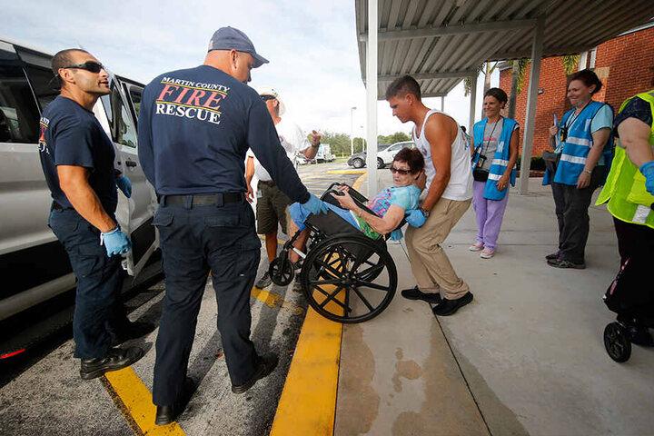 Rettungskräfte von der Feuerwehr bringen Anwohner in eine Notunterkunft. Wegen des herannahenden Hurrikans «Dorian» haben einige Küstengebiete in den USA eine Evakuierung angeordnet.