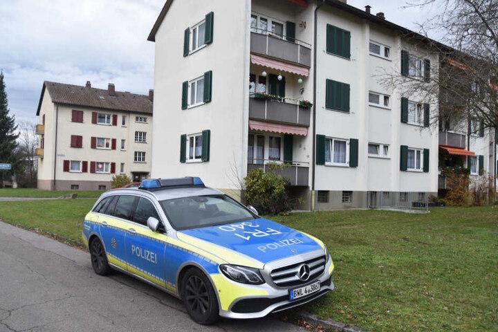 Ein Polizeiauto steht am Sonntag vor den Mehrfamilienhäusern.