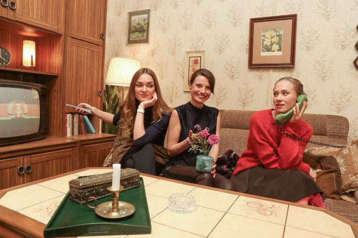 """Die Schauspielerinnen Josefine Busch (l-r), Julia Hartmann und Alina Levshin sind bei der Premiere der Amazon-Serie """"Deutschland86"""" im Kino International und sitzen in einer Wohnzimmer-Deko."""
