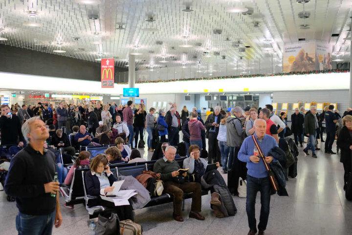 Reisende warten nach dem Zwischenfall auf dem Flughafen.