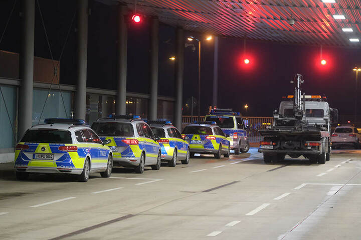Ein Abschleppwagen steht auf dem Flughafen an der Vorfeldschranke nahe Terminal A neben Polizeiautos.