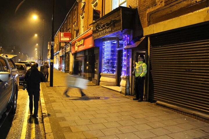 Ein Polizist steht in Birmingham vor einem Wohnhaus. Bewaffnete Polizisten hatten in dem Haus eine Wohnung gestürmt.