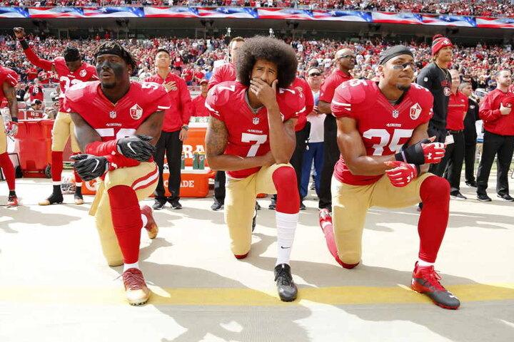 Kaepernick (Mitte) hatte 2016 damit begonnen, bei der Hymne der NFL-Spiele aus Protest gegen Rassismus und Polizeigewalt auf die Knie zu gehen.