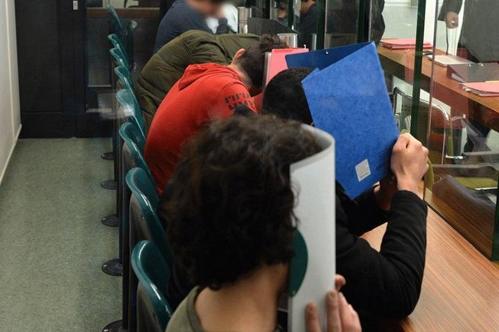 Die Angeklagten verstecken ihre Gesichter hinter Ordnern. Fünf von ihnen können jetzt die U-Haft verlassen.