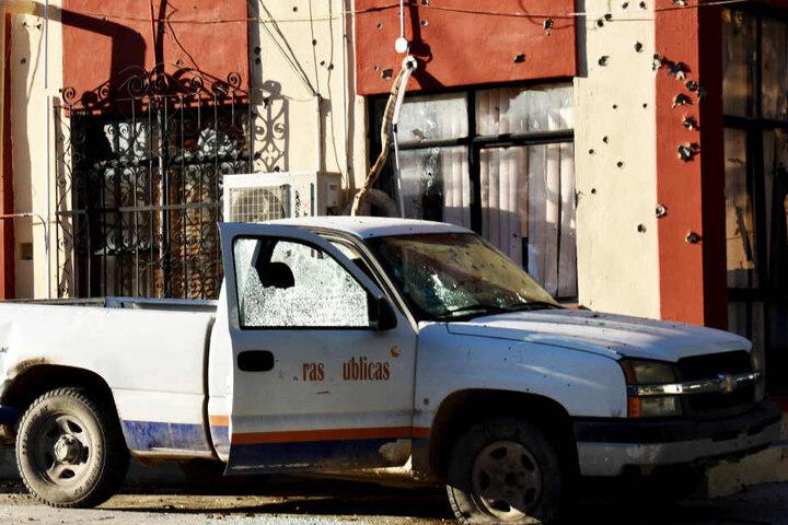 Ein beschädigtes Fahrzeug steht vor dem Rathaus der Stadt Villa Union, dessen Fassade mit Einschusslöchern übersät ist.