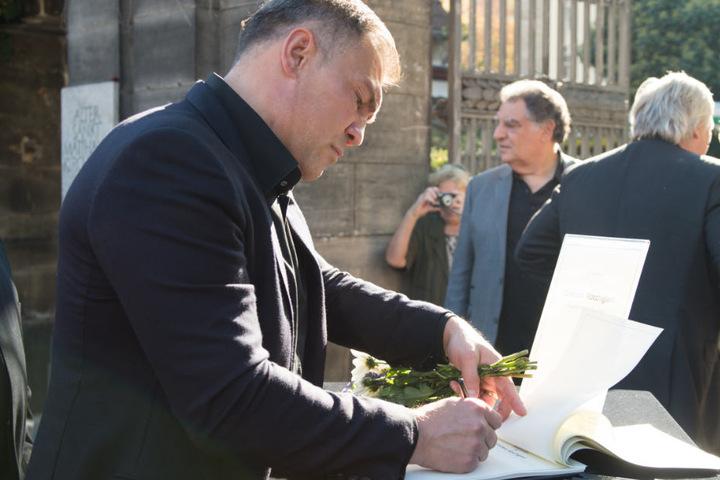 Der ehemalige Boxer Dariusz Michalczewski trägt sich in eine Kondolenzliste am Eingangstor zum Friedhof ein.