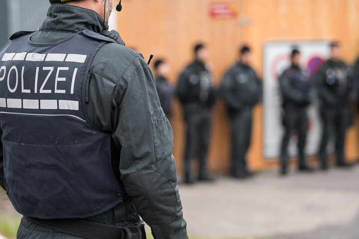 Beamte der Polizei steht während eines Einsatzes vor einem Gebäude. (Symbolbild)
