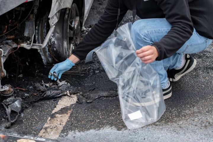Ein Kriminalbeamter sichert an einem ausgebrannten Fahrzeug Spuren.