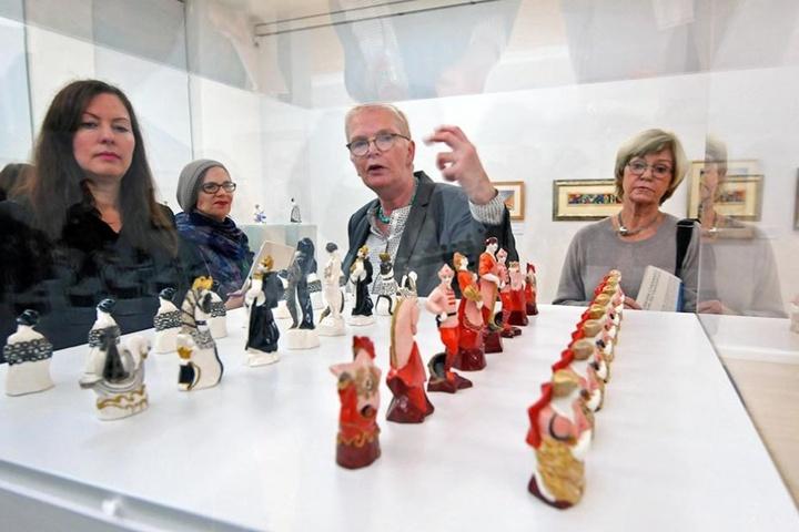 Kuratorin Katharina Metz vor einem Schaukasten mit Schachfiguren.