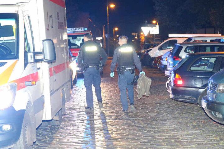 Zwei Polizisten gehen die Straße entlang, der rechte hält eine Wolldecke in der Hand.