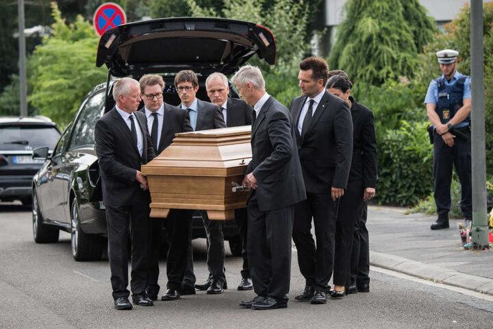 Die Männer bringen den Sarg in einen Leichenwagen.