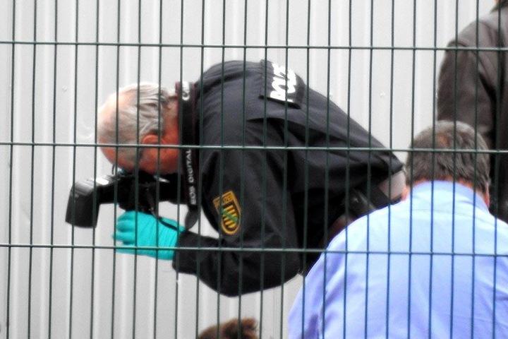 Ein Beamter fotografiert verschieden sichergestellte Gegenstände und Kleidungsstücke vor dem Asylheim.