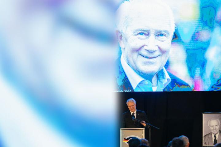 ESA-Astronaut Thomas Reiter spricht. Hinter ihm ein Porträt des Verstorbenen.
