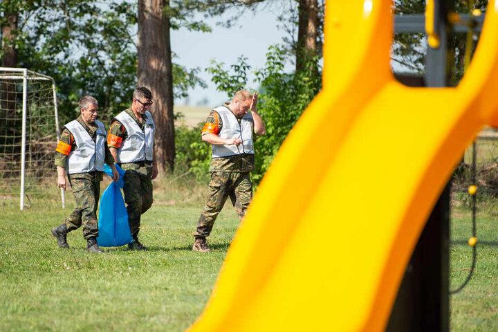 Mitarbeiter der Bundeswehr haben in ihrem blauen Müllsack ein Wrackteil, das auf die Spielwiese eines Kindergartens geknallt war.