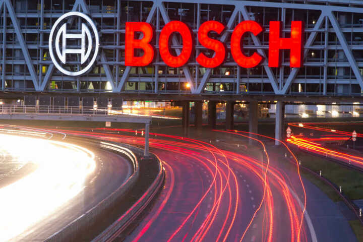 Autos fahren auf der Autobahn 8 unter einer Brücke mit dem Bosch-Logo entlang.