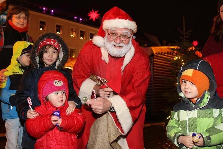 Sehnsüchtig warten die Kinder auf dem Weihnachtsmarkt in Pirna, dass der Weihnachtsmann Süßes verschenkt.