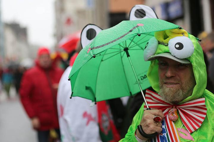 Ein wetterfester Karnevalist schaut sich die Schull- und Veedelszöch an.