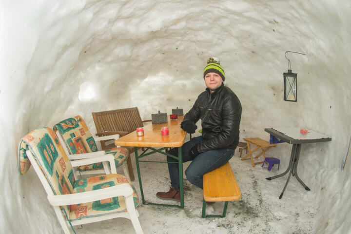 Im Iglu stehen Gartenstühle mit Sitzauflagen, Bänke und ein Bierzelttisch.