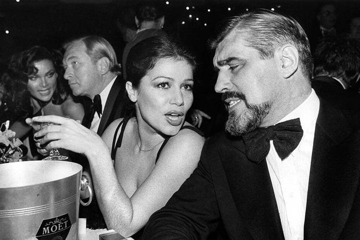 15.01.1977: Hannelore Elsner und der Schauspieler und Mario Adorf sitzen während des Deutschen Filmballs in München.