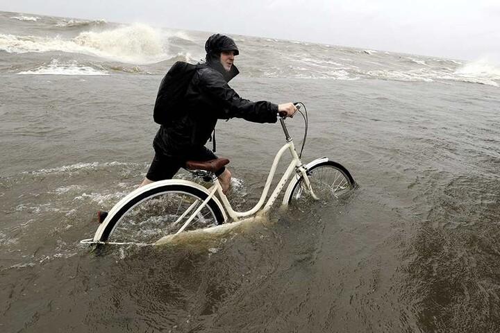 """Tyler Holland schiebt sein Fahrrad durch Wasser, das durch Tropensturm """"Barry"""" aus dem Lake Pontchartrain über den Damm geschoben wurde."""
