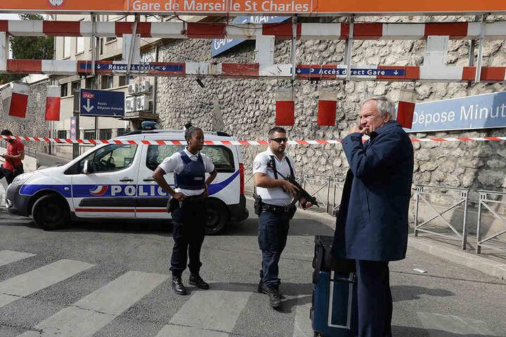 Ein Fahrgast und zwei Polizisten stehen in Marseille vor dem Bahnhof.