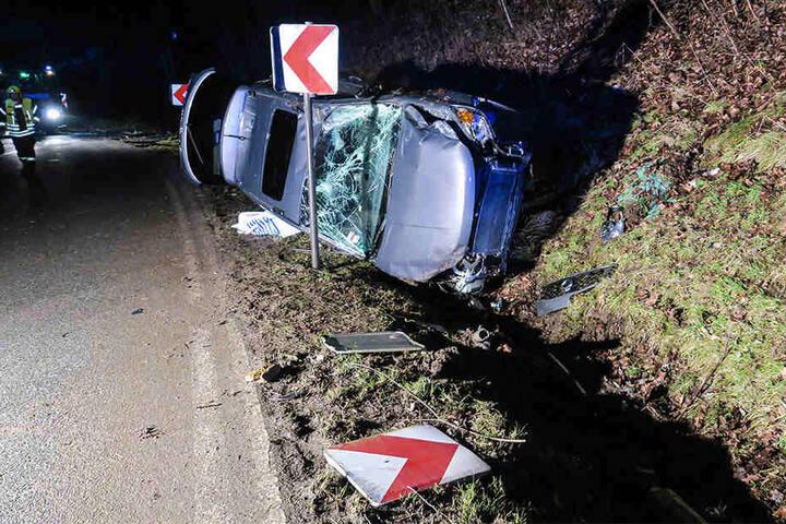 Das Auto blieb nach der Kollision mit einem Schild auf der Seite in einem Graben liegen.