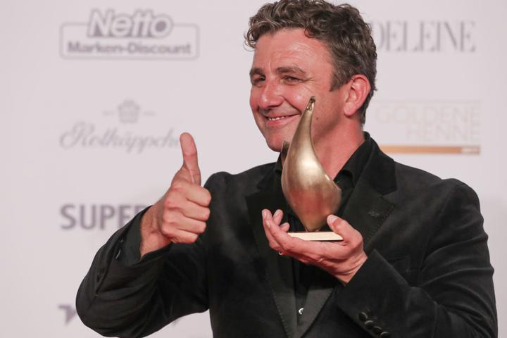 """Der Schauspieler Hans Sigl posiert mit der Goldenen Henne, die er in der Kategorie """"Schauspiel"""" erhalten hat."""