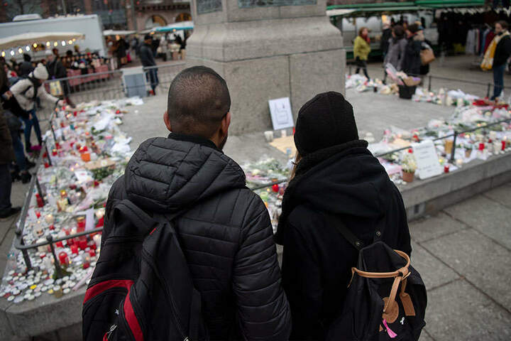 Stilles Gedenken: Zwei junge Menschen stehen in Straßburg vor einem Kerzenmeer.