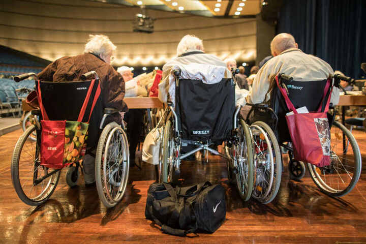Drei ältere Menschen in Rollstühlen in einer Sammelstelle. Viele Menschen sind auf die Hilfe anderer bei der Evakuierung angewiesen.