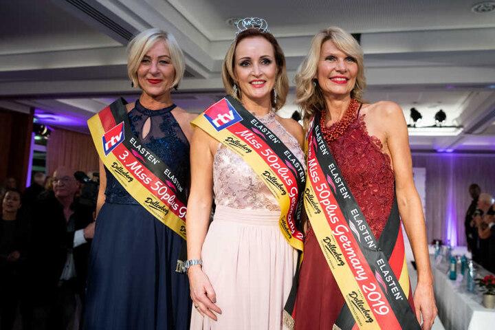 Evelyn Reißmann (Mitte), Siegerin bei Miss 50plus Germany 2019, steht zwischen der Drittplatzierten Marion Ellendorff (l) und der Zweitplatzierten Eva Möller-Westman.