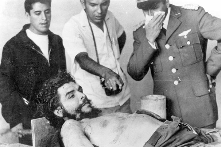 """Trotz offener Augen: Das Foto zeigt den toten Che, """"begutachtet"""" von Armeeoffizieren  und Reportern."""