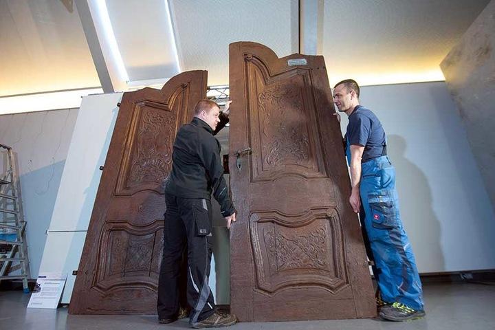 René Lübeck (38, l.) und Sandro Frenzel (42) werkeln am größten Ausstellungsstück der Sonderausstellung 900 Jahre Zwickau: eine 2,60 Meter hohe Gaststättentür aus dem 18. Jahrhundert. Sie wurde beim Abriss der Zwickauer Altstadt gerettet.