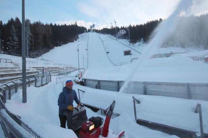 Marcus Stark vom VSC ist mit der Schneefräse unterwegs, um die Zuschauertraversen von der weißen Last zu befreien.