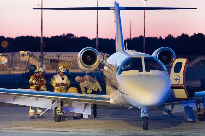 Flughafenfeuerwehr und Pilot Ulrich Marseille begutachten die Maschine.
