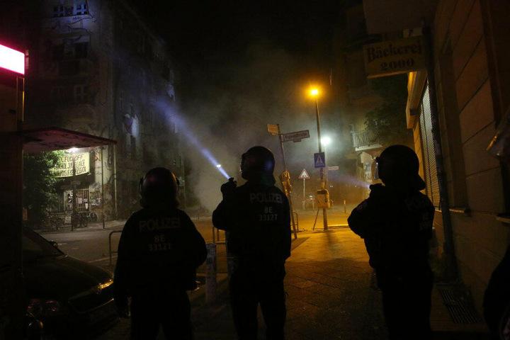 Die Polizisten versuchen, mit Taschenlampen die Steinewerfer ausfindig zu machen.