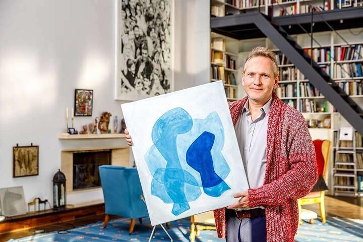 """Architekt Jens Heinrich Zander (48) zeigt im Wohnzimmer von Stefan Heinemann (67) das Ölbild """"Layers"""" von Christof Kraus, das auf dem Kunstmarkt für 750 Euro angeboten wird."""