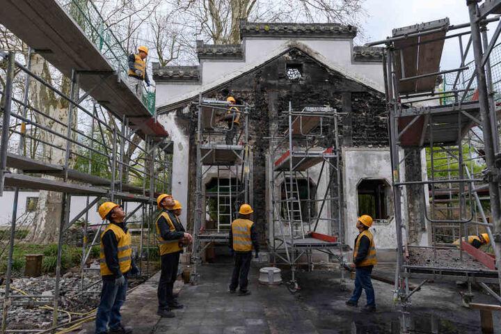 Spezialisten aus China bauen den Pavillon wieder auf.