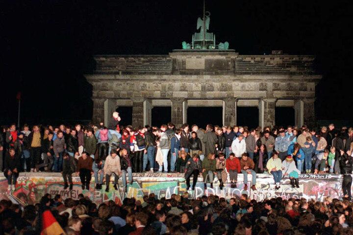 Jubelnde Menschen auf der Berliner Mauer am Brandenburger Tor am 10. November 1989.