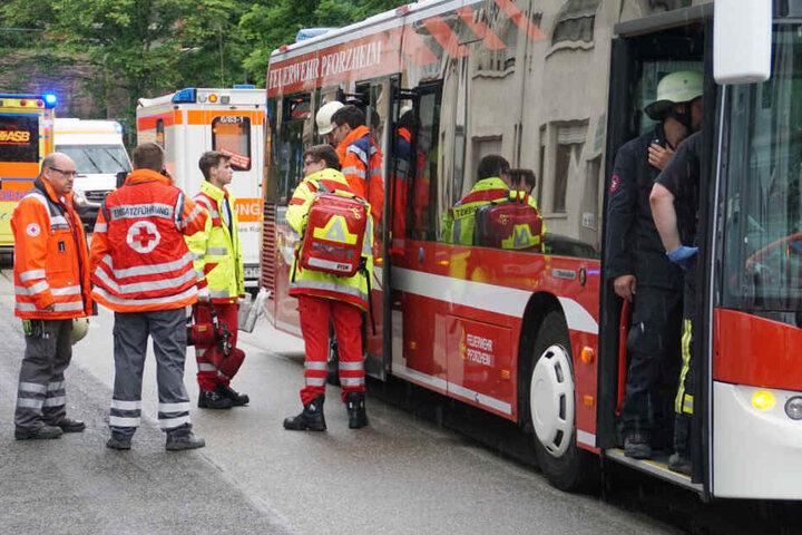 Rettungskräfte vor einem Bus der Feuerwehr.