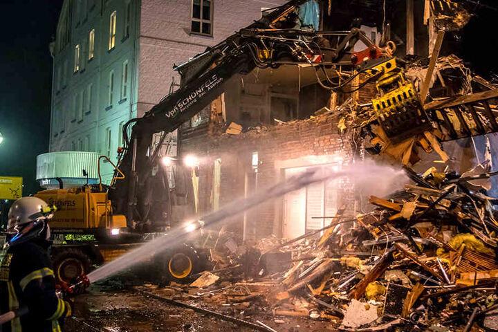Die Feuerwehr unterstützt die Abrissarbeiten an dem abgebrannten Gebäude.