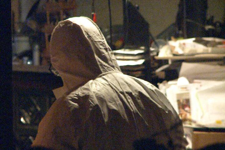 Durch die Fensterscheibe des Hauses ist ein Ermittler in einem weißem Ganzkörperanzug zu sehen.