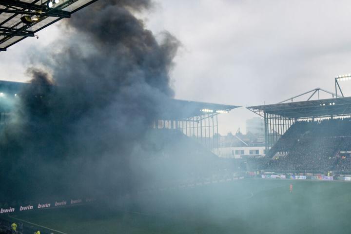 Nach einer Pyro-Aktion von HSV-Fans zieht eine schwarze Rauchwolke durch das Millerntor-Stadion.