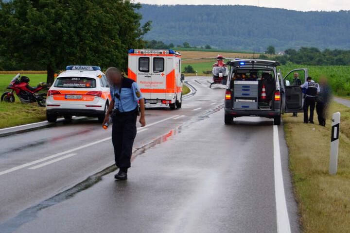 Ein Polizist geht über die nasse Fahrbahn.