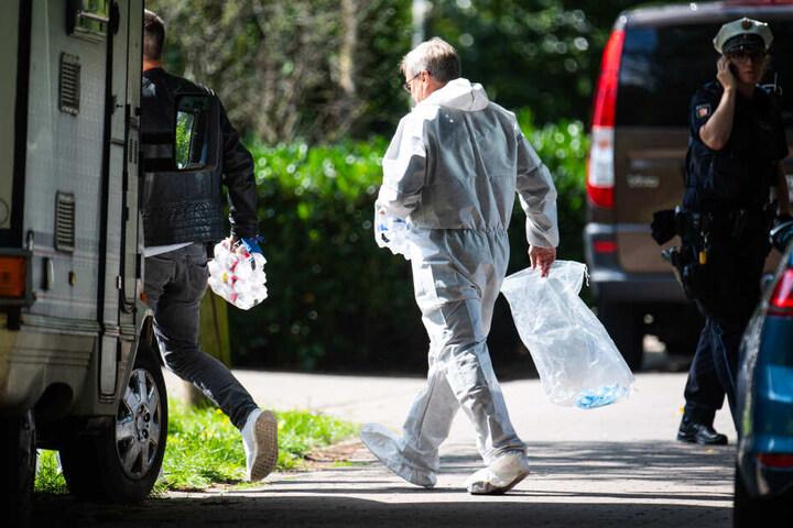 Polizisten und Beamte der Spurensicherung gehen zu dem Wohnhaus, in dem die Leiche einer Frau gefunden wurde.