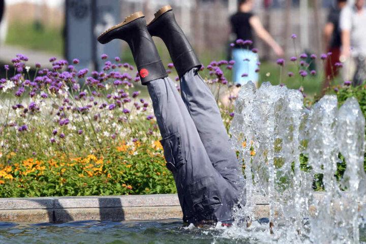 Aus einem Brunnen ragen zwei Beine mit Gummistiefeln.