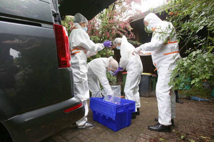 Ermittler der Mordkommsion stehen in weißen Schutzanzügen vor einem Haus, in dem zuvor ein Mann erschossen wurde.