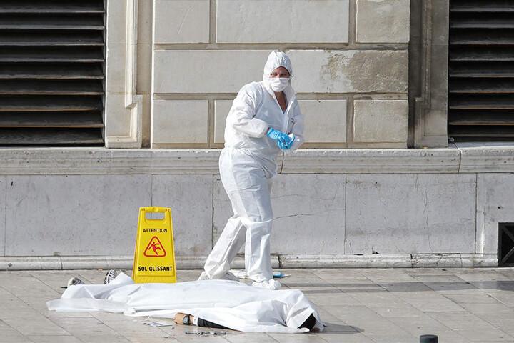 Ein Mitglied der Spurensicherung untersucht vor dem Bahnhof eine Leiche.