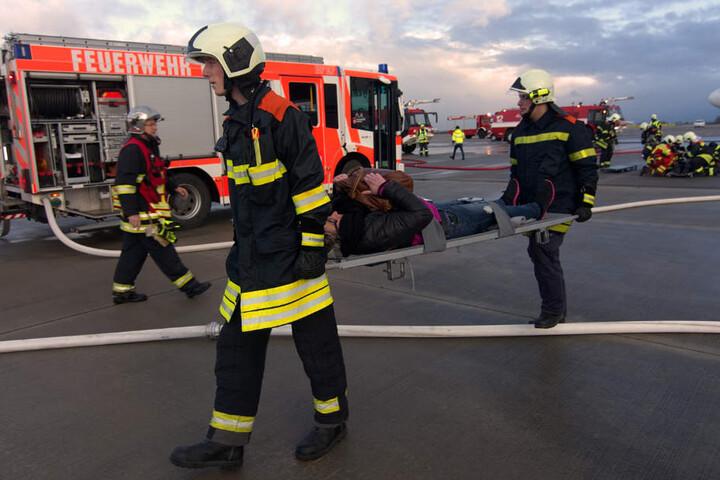 Feuerwehrmänner bringen eine Verletzte zur Patientenablage.