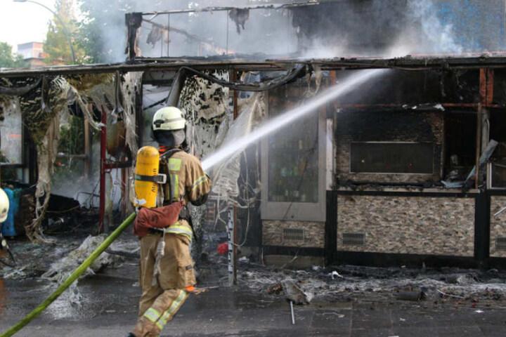 Ein Berliner Feuerwehrmann löscht die letzten Flammen.