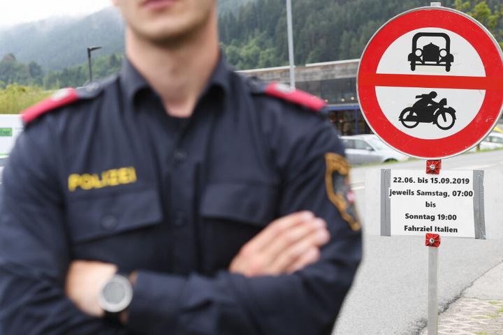 Ein Polizist steht vor einem Schild, das auf die Sperrung für den Verkehr mit Fahrziel Italien hinweißt.